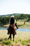 Cowboy riding his horse. With lake in the background stock photos