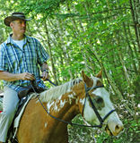 Cowboy Riding Horse. A mature man on a trail ride in New Brunswick with an Appaloosa horse Royalty Free Stock Image