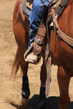A cowboy riding a horse. A close up view of a cowboy riding his horse with his boot and stirrup Stock Image