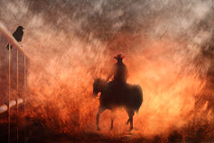 Cowboy riding on a horse III. Abstract horse and cowboy rider going into a fire with a crow on a fence. This image can be changed to a vertical format stock photo