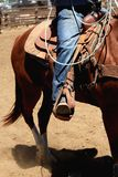 Cowboy riding a horse with the stirrup in front. A cowboy riding a horse in a rodeo showing the boot, stirrup, jeans and saddle Royalty Free Stock Image
