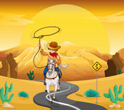 A cowboy riding on a horse travelling through the desert. Illustration of a cowboy riding on a horse travelling through the desert Royalty Free Stock Image