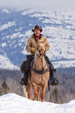 Cowboy riding up a mountain Stock Photography