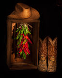 Cowboy Ristra Closet. Close Up of Cowboy Boots, Cowboy Hat, and Pepper Ristra in Wooden Crate royalty free stock images