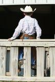 Cowboy s'asseyant sur la frontière de sécurité en bois Photographie stock
