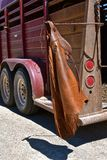 Cowboy`s chaps hanging from trailer latch. A cowboy`s pair of chaps are left hanging on the trailer which transports his horse stock photography
