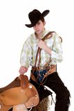 Cowboy with saddle and rein Royalty Free Stock Image