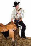 Cowboy with saddle and rein Stock Image