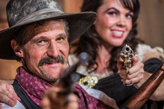 Cowboy and Saloon Girl Point Weapons Stock Photography