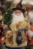Cowboy Santa Claus dans le manteau de shearling avec la selle et la lanterne et l'arbre de Noël - foyer sélectif - fond brouillé photos stock