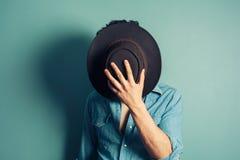 Cowboy se cachant derrière son chapeau Photographie stock libre de droits