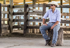 Cowboy seated. On a farm Royalty Free Stock Photography