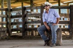 Cowboy seated. On a farm stock photos