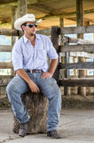 Cowboy seated. On a farm Royalty Free Stock Images