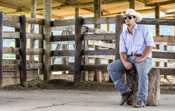 Cowboy seated. On a farm Royalty Free Stock Image