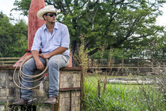 Cowboy seated. On a farm Stock Images