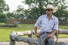 Cowboy seated. On a farm Royalty Free Stock Photo