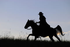 Cowboy silhouette. Cowboy galloping across a Montana ridge silhouetted against dawn sky Stock Photography
