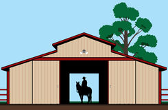 Cowboy in Silhouette. Cowboy is astride his horse in the shadow of a barn Stock Image