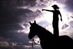 Cowboy Silhouette Standing on Horse Royalty Free Stock Photos