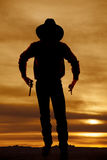 Cowboy silhouette two guns. A silhouette of a cowboy holding onto his pistols Royalty Free Stock Photos