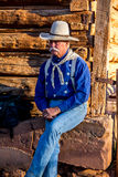 Cowboy Sitting at the Barn. Cowboy sitting at the old log barn. The light is warm colored as it is early morning royalty free stock photography