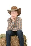 Cowboy sitting on hay bale Stock Images
