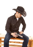 Cowboy sitting holding a gun Royalty Free Stock Photo