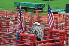Cowboy Sitting on Red Fencing. A cowboy sitting on some red fencing bordered by American flags on either side, getting ready for the rodeo to begin at the Stock Images