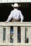 Cowboy sitting on wooden fence. A view of the back of a young boy in cowboy clothing as he sits on a wooden fence Stock Photography