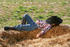 Cowboy Sleeping. Little Cowboy Sleeping in the Straw with Hat on Head stock image