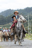 Cowboy with sleeping toddler riding horse in Ecuador. May 27, 2017 Sangolqui, Ecuador: cowboy with sleeping toddler in his arms riding horse on a country road Stock Images