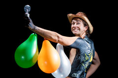 Cowboy with smile and body art. Happy handsome cowboy with lamp and baloons isolated with stupid smile isolated over black background Royalty Free Stock Images