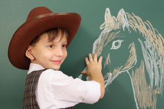 Cowboy. Smiling child as a cowboy and his horse Royalty Free Stock Photography