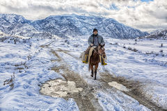 Cowboy In Snowy Winter Desert, the image on the background of the solar sky. Horserider in Caucasian mountains   wilderness.JAN, 2 Stock Photos