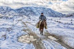 Cowboy-In Snowy Winter-Wüste, das Bild auf dem Hintergrund des Solarhimmels Horserider in der kaukasischen Gebirgswildnis JAN., 2 Stockfotos