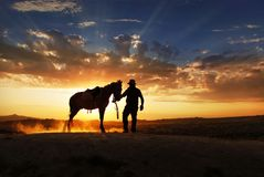 A  cowboy is standing with his horse. A cowboy stending with his horse and horse is making dust with its  feet Stock Photo