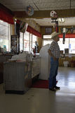 Cowboy standing inside of Hokes Cafe stock photography