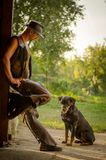 Cowboy stands with dog at the barn. A handsome man with a hat. Cowboy stands at barn with dog. A handsome man with a hat. A female idol with a muscular body. A Stock Photos