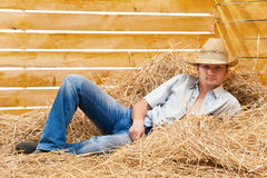 Cowboy on straw. Young man in a cowboy's hat on straw in a thematic corner of a photographic studio Stock Image