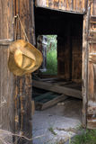 Cowboy straw hat and opened doors of old barn. Looking through the open doors of old barn with a cowboy straw hat hanging on wall Stock Photography
