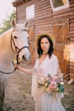 Cowboy style bride standing near horse, close up stock photography