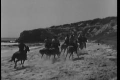 Cowboy sull'equitazione galoppante attraverso la spiaggia con seguire del cane archivi video