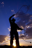 Cowboy swing rope. A cowboy silhouetted in the sunset twirling a rope Royalty Free Stock Image