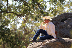 The cowboy thinker. A cowboy sits on a boulder under an oak tree Stock Photos