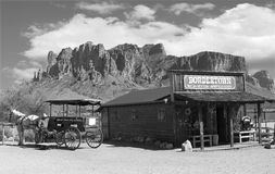 Cowboy Town. Old black and white Wild West Cowboy town with horse drawn carriage and mountains in background Royalty Free Stock Photos