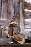 Cowboy Toys. Rifle, lariet, cowboy hat, and spurs at back door of old log house Stock Photos