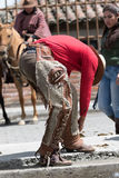 Cowboy tying chaps to boots in Ecuador. June 10, 2017 Toacazo, Ecuador: man arranging his chaps before rodeo stock photos