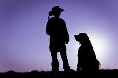 Cowboy u. sitzendes Hundeschattenbild Lizenzfreies Stockbild