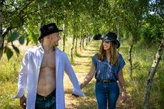 Cowboy- und Cowgirlpaare mit den Hutgriffhänden, wie sie durch Allee von Bäumen auf Ranch gehen lizenzfreies stockbild